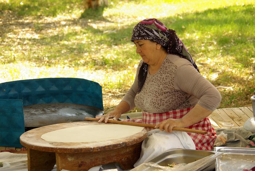 Женщина готовит традиционную турецкую лепешку, Турция.